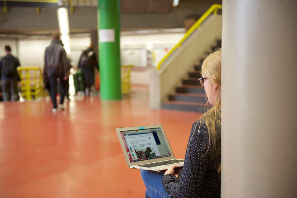 student in the foyer using her laptop